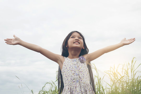 Cute Asian Girl raised hand at meadow  happily.
