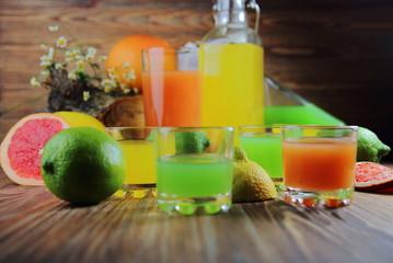 цитрусовые соки в рюмках с лимоном,лаймом и грейпфрутом