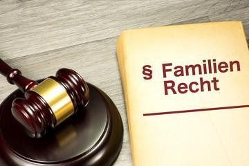 Ein Richterhammer und ein Gesetzbuch mit Familienrecht für eine Scheidung
