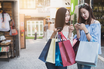 Two beautiful girls with shopping bags walking at the mall Business shopping situation idea concept.