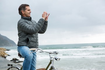 Man on bicycle taking picture on mobile phone