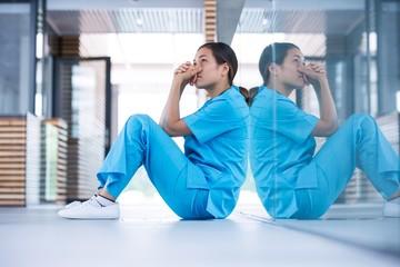Worried nurse sitting on floor