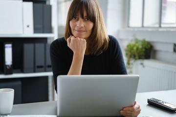 frau arbeitet mit laptop am schreibtisch