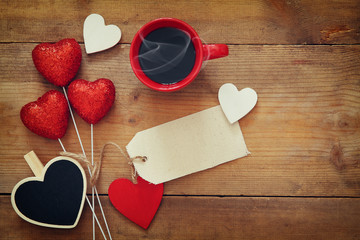 Red hearts and cup of coffee on wooden background