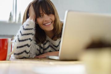 frau sitzt am laptop und stützt lachend den kopf auf