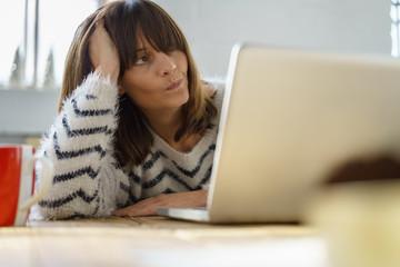 frau sitzt am laptop und schaut nachdenklich zur seite