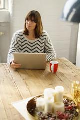 frau sitzt mit laptop am tisch und schaut nachdenklich nach oben