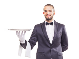 Waiter in tuxedo and gloves holding empty tray and napkin over w