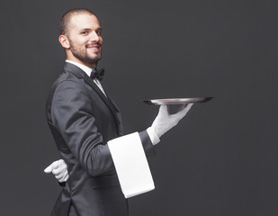 Happy smiling waiter in black suit holding a silver tray over da