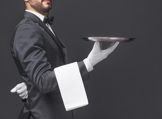 Cropped image of a waiter in black suit holding a silver tray ov