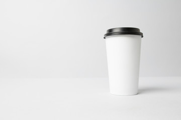White paper cup with a black cap mockup