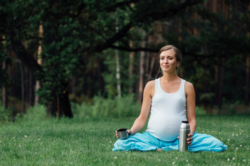 pregnant yoga in the lotus position with thermos. in the park on the grass , outdoor, health woman, female.