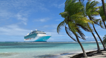 Tropical beach with palmtrees and luxury cruise ship on crystal clear Caribbean Sea.