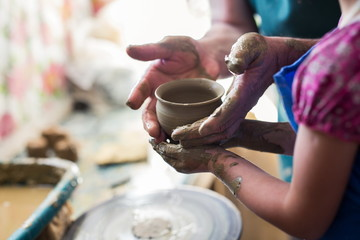 Senior potter teaching a little girl the art of pottery. Child working with clay, Creating ceramic pot on sculpting wheel. Concept of mentorship, generations. Arts lessons, pottery workshop for kids
