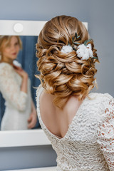 rear view of a bride with curly wedding hairstyle with cotton flowers as winter image