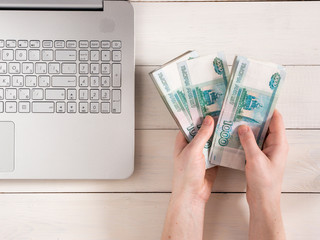 Hands holding russian rubles near laptop