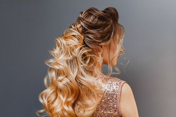 Rear view of a woman with dyed hair with a beautiful evening or wedding hairdo