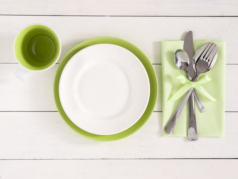Empty plates, cup and silverware on white wooden background