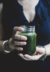 Female hands holding green smoothie