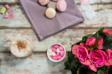 Flower vase, macaroons and cup of coffee