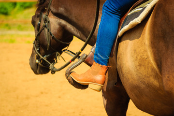 Woman foot in stirrup on horse saddle