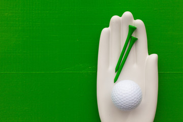 Detail of ceramic hand with golf equipments