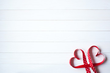 Wooden background with red hearts from ribbon