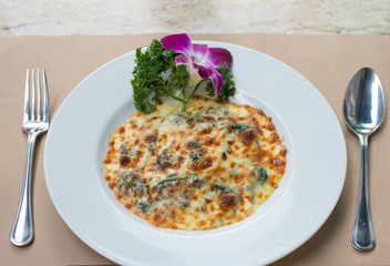 Spinach with cheese baked on white plate,Italian food