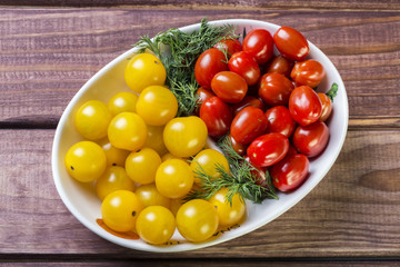 Bunch of red and yellow cherry tomatoes with dill in a bowl. Top view