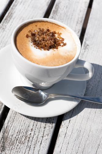 cappuccino trinken in der sonne wei er holztisch. Black Bedroom Furniture Sets. Home Design Ideas