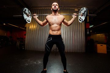 Muscular man training squats with barbells at gym