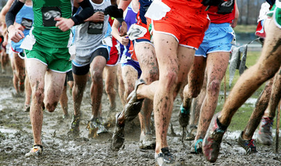 High school boys racing cross country in the mud