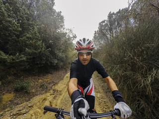 POV, Original point of view. Happy Young man on bicycle take a selfie with action cam and selfie stick. Training on mountain bike on a mountainous road in a rainy day