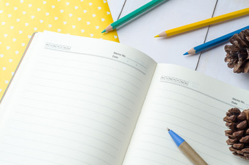 Blank daily planner notebook with pen and color pencils on white