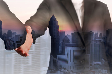 Double exposure of handshake, cityscape and sunset at evening as Commitment concept.