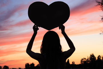 Female silhouette on sunset background with heart shape in hands