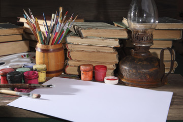 Acrylic paints, an easel, a blank sheet of white paper, painted by the artist, books and old kerosene lamp on the desktop. Photo in old style