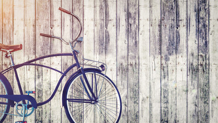 Vintage bicycle parked beside wooden wall.