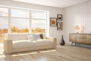 White room with sofa and autumn landscape in window. Scandinavian interior design