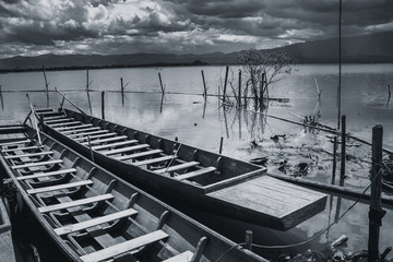 empty twin wooden fishing boat in rain storm in quiet lake sky black and white tone.