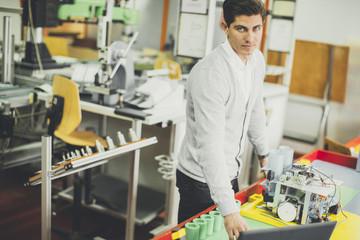 Young man in robotics classroom