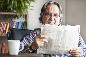 Senior man reading newspaper