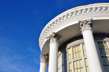 Looking up at a white round classical building with columns and capitals against the blue sky.