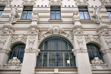Looking up at the facade of old building with sculptures of human heads in Art Nouveau style (Jugendstil) and wide arched windows. Riga, Latvia.