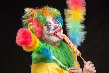 Scary clown with mohawk and a smile with a lollipop on a black b