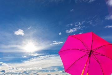 Obraz parasol rose sur fond de ciel ensoleillé  - fototapety do salonu