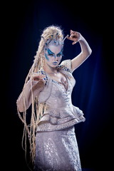 emotional actress woman in makeup and costume queen of elves or snow queen on blue-black background