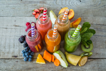Selection of colourful smoothies on rustic wood background