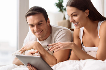 Joyful young couple using a tablet