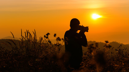 Silhouette of a young who like to travel and photographer